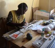 Empowering Women in Development member using knitting machine.